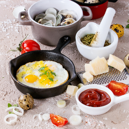 Breakfast with fried quail eggs in iron cast pan, cherry tomatoes, onion, ketchup sauce, seasonings in mortar, cheese grater, egg shell in pot. Beige concrete texture background. Square image