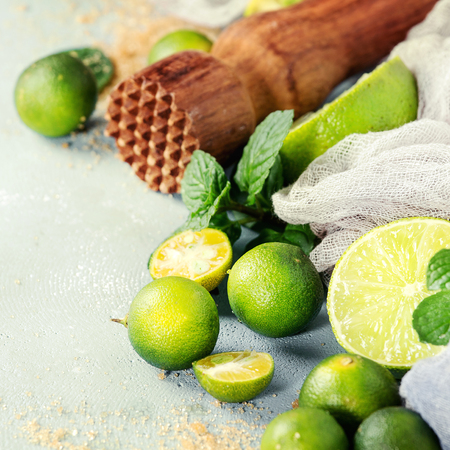 Ingredients for mojito cocktail, whole, sliced lime and mini limes, mint leaves, brown crystal sugar over gray stone texture background with gauze textile and wooden bar muddler. Close up. Square image Stock Photo