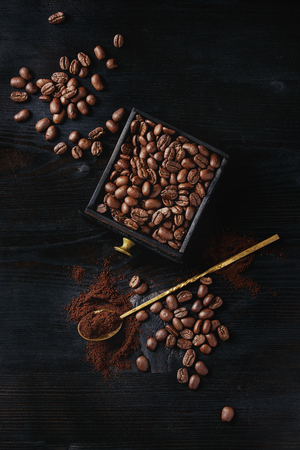 Roasted coffee beans and grind coffee in wood box with spoon over black wooden burnt background. Top view with space.