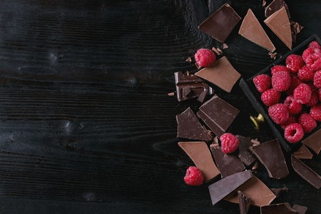 Dark and milk chopping chocolate and chips shavings chopping chocolate with fresh raspberries in black wood box over black burnt wooden background. Top view with space. Chocolate dessert concept 版權商用圖片