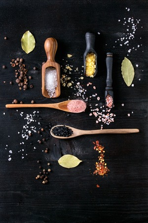 sel: Variety of different colorful salt yellow saffron, pink, black himalayan, white sea and fleur de sel in wooden spoons with black, chili, allspice pepper over black burnt wood background. Top view Stock Photo