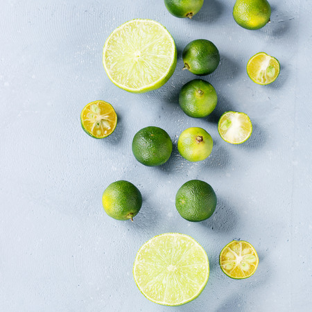 Whole, sliced lime and mini limes over gray stone texture background. Top view, space. Square image Stock Photo