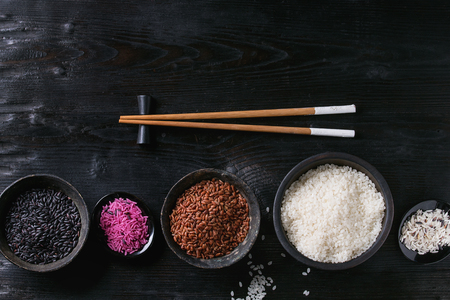 Surtido de la variedad de arroz crudo crudo blanco, negro, marrón, rosa en cuencos negros sobre fondo de madera quemada con los palillos. Vista superior con espacio Foto de archivo - 75360568