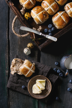 Hot cross buns in wooden tray served with butter, knife, blueberries, easter eggs, birch branch, jug of cream on textile napkin over old texture wood background. Top view, space. Easter baking. Stock Photo - 75360813