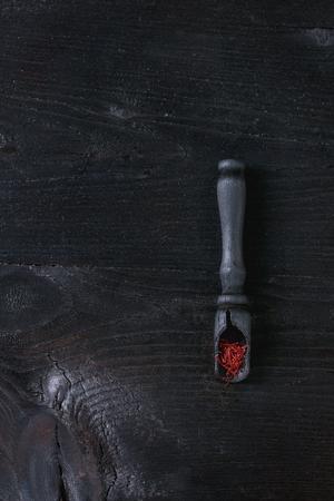 Rohes organisches rotes Safrangewürz in den hölzernen Löffeln über Schwarzem gebranntem hölzernem Hintergrund. Draufsicht mit Platz Standard-Bild - 75360819