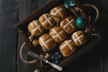 Hot cross buns in wooden tray served with butter, knife, blueberries, easter eggs, birch branch over old texture wood background. Top view, space. Easter baking.