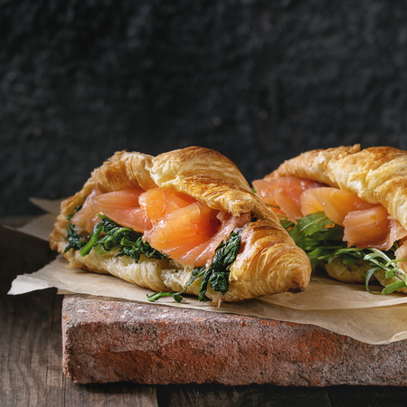 Two croissant with smoked salted salmon, spinach and arugula served on baking paper terracotta board over dark old wooden background. Copy space. Square image