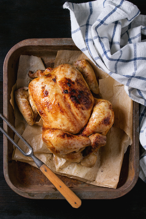 white backing: Grilled baked whole organic chicken on backing paper in old oven tray with white kitchen towel and meat fork over black burnt wooden background. Top view with space.