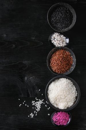 Variedade da variedade do arroz colorido cru cru branco, preto, marrom, rosa em umas bacias pretas sobre o fundo de madeira queimado. Vista superior com espaço para texto Foto de archivo - 75361040