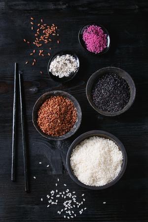 Surtido de la variedad de arroz crudo crudo blanco, negro, marrón, rosa en cuencos negros sobre fondo de madera quemada con los palillos. Vista superior con espacio Foto de archivo - 75361044