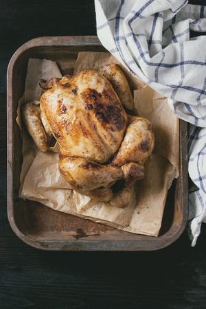 white backing: Grilled baked whole organic chicken on backing paper in old oven tray with white kitchen towel over black burnt wooden background. Top view with space. Stock Photo