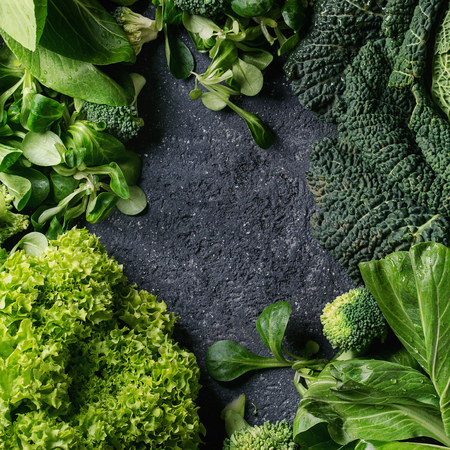 Variety of raw green vegetables salads, lettuce, bok choy, corn, broccoli, savoy cabbage as frame over black stone texture background. Top view, space for text. Square image