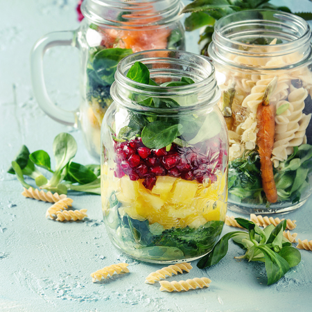Variety of salads in mason jars. Fruit salad mango, pomegranate, greens, vegetables, wholegrain pasta, carrots and cauliflower, salmon. Standing over blue texture background. Food to go. Square image Stock Photo