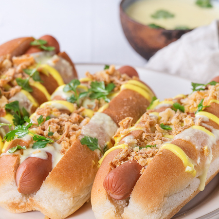 Hot dogs with sausage, fried onion, coriander leaves, cheese sauce and mustard, served on white ceramic plate with textile over white concrete texture background. Fast food. Close up. Square image