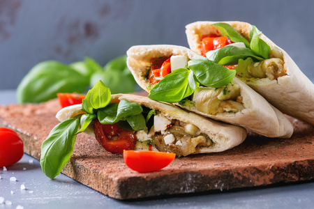 Pita bread sandwiches with grilled vegetables paprika, eggplant, tomato, basil and feta cheese served on terracotta board over gray stone background. Close up. Healthy fast food concept. Reklamní fotografie