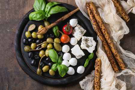 antipasto platter: Mediterranean appetizer antipasti board with green black olives, feta cheese, mozzarella, capers, pepper, basil with grissini bread sticks over old wooden background. Top view with space