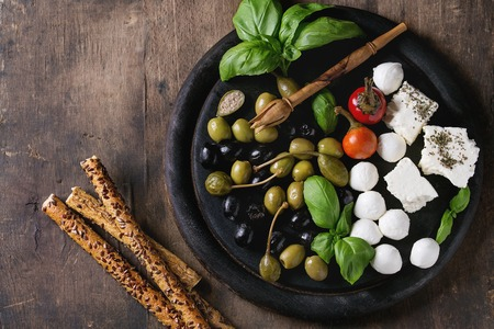 caper: Mediterranean appetizer antipasti board with green black olives, feta cheese, mozzarella, capers, pepper, basil with grissini bread sticks over old wooden background. Top view with space