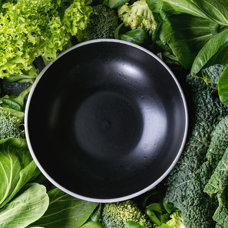 Variety of raw green vegetables salads, lettuce, bok choy, corn, broccoli, savoy cabbage round empty black ceramic bowl. Food background. Top view, space for text. Square image Banco de Imagens