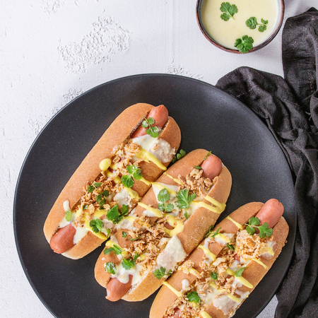 Hot dogs with sausage, fried onion, coriander leaves, cheese sauce and mustard, served on black ceramic plate with textile over white concrete texture background. Fast food. Top view. Square image
