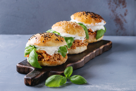 Homemade mini burgers with pulled chicken, basil, mozzarella cheese and yogurt sauce on wooden serving board over gray texture background. Healthy fast food concept 版權商用圖片