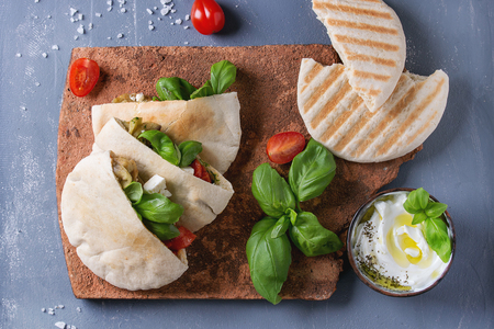 Pita bread sandwiches with grilled vegetables paprika, eggplant, tomato, basil and feta cheese served on terracotta board over gray stone background. Healthy fast food concept. Top view with space Reklamní fotografie