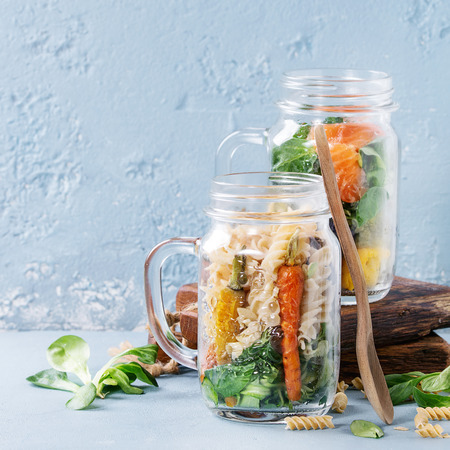 Variety of vegetable salads in mason jars. Salad with greens, pasta, carrots, cauliflower, salmon. Standing with wooden spoon and serving board over blue texture background. Food to go. Square image Stock Photo