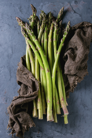 Bundle of young raw uncooked organic green asparagus on sackcloth rag over gray blue metal texture background. Top view. Healthy eating