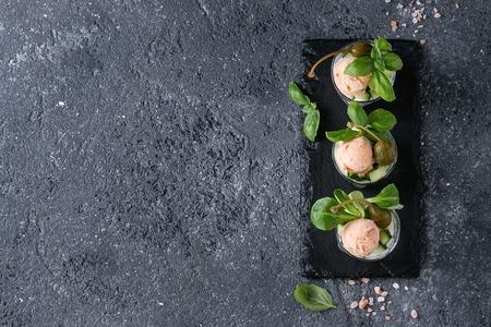 Het voorgerecht van Verrines met zalmpastei, rode kaviaar, komkommer, roomkaas, kruiden, kappertjes in glazen diende met roze zout en basilicum op de zwarte raad van de leisteen over grijze textuurachtergrond. Bovenaanzicht Stockfoto