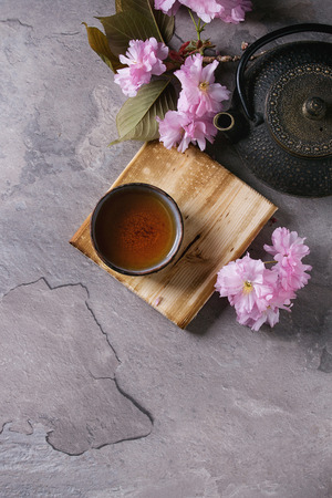 Black iron teapot and traditional ceramic cup of tea on wooden serving board with blossom pink flowers cherry branch over gray texture background. Top view with space Stock Photo
