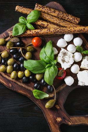 caper: Mediterranean appetizer antipasti board with green black olives, feta cheese, mozzarella, capers, pepper, basil with grissini bread sticks over black wood burnt background. Top view with space Stock Photo