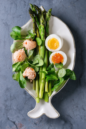 Cooked green asparagus with half boiled egg, salad, red caviar and salmon pate served on white fish shape plate over gray blue texture metal background. Top view, fine dining Stock Photo