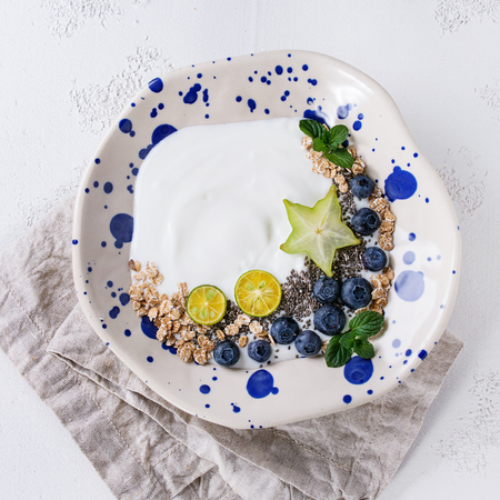 Smoothie bowl healthy breakfast. Yogurt with blueberries, granola, chia seeds, lime, mint and carambola on textile napkin over white concrete texture background. Top view, space.
