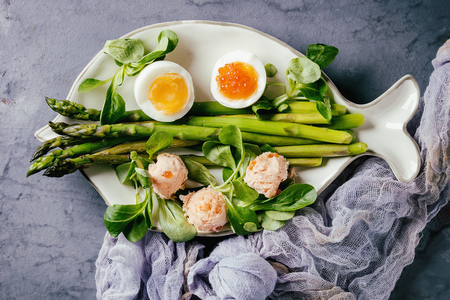 Cooked green asparagus with half boiled egg, salad, red caviar and salmon pate served on white fish shape plate with gauze textile over gray blue texture metal background. Top view, toned image Stock Photo