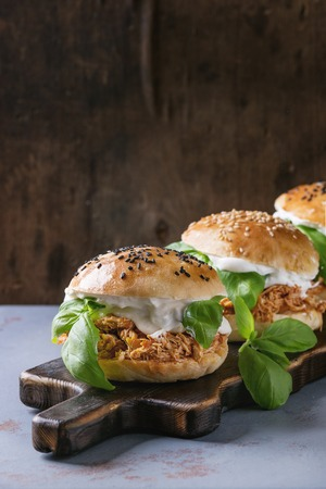 Homemade mini burgers with pulled chicken, basil, mozzarella cheese and yogurt sauce on wooden serving board over gray texture background.
