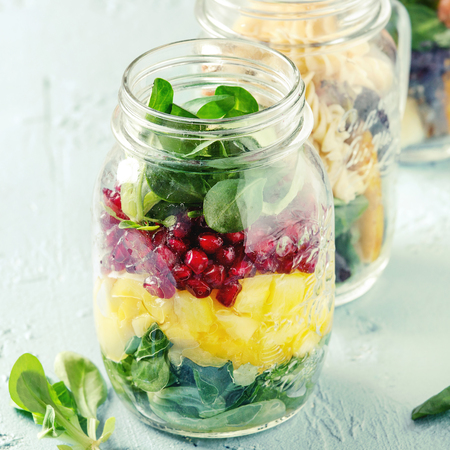 Variety of salads in mason jars. Fruit salad mango, pomegranate, greens, vegetables, wholegrain pasta, carrots and cauliflower, salmon. Standing over blue texture background.