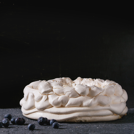 Homemade meringue basis for cake Pavlova with fresh blueberries on black concrete texture background. Copy space. Square image