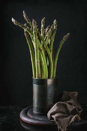 Bundle of young raw uncooked organic green asparagus in old tin jar on wooden chopping board over black background.