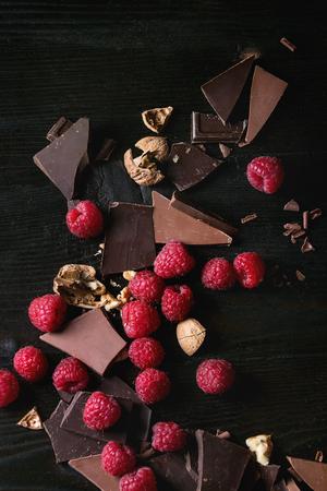 ダークとミルクの新鮮なラズベリーとチョコレートを刻んでチョコレートとチップの削りくずをチョッピング ヒープし、黒焦げた木背景にクルミを 写真素材