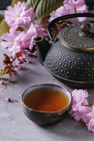 Black iron teapot and traditional ceramic cup of tea with blossom pink flowers cherry branch over gray texture background. Asian style. Stock Photo