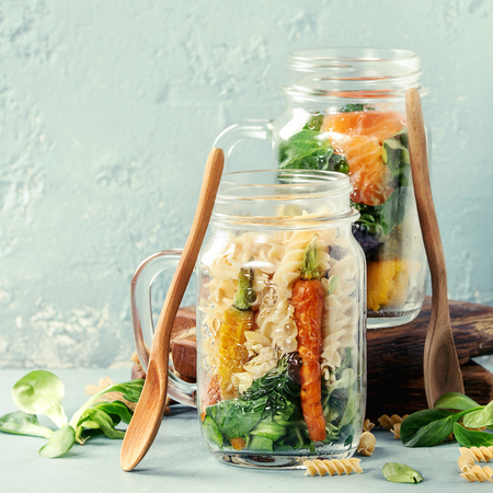 Variety of vegetable salads in mason jars. Salad with greens, pasta, carrots, cauliflower, salmon. Standing with wooden spoon and serving board over blue texture background.