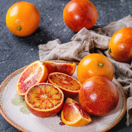 Sliced and whole ripe juicy Sicilian Blood oranges fruits with sackcloth rag on ceramic plate over black concrete texture background. Square image Stock Photo