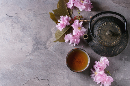 Black iron teapot and traditional ceramic cup of tea with blossom pink flowers cherry branch over gray texture background. Top view with space, Asian style.