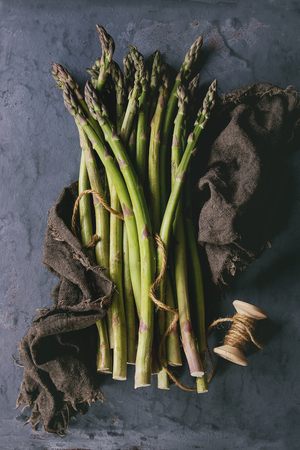 Bundle of young raw uncooked organic green asparagus on sackcloth rag over gray blue metal texture background. Top view.
