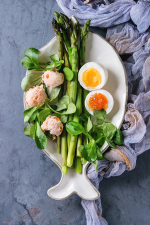 Cooked green asparagus with half boiled egg, salad, red caviar and salmon pate served on white fish shape plate with gauze textile over gray blue texture metal background. Stock Photo
