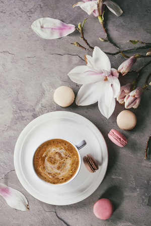 White cup of black coffee, served on white saucer with macaroons biscuits and magnolia flower blossom branch over gray texture background. Flat lay, space