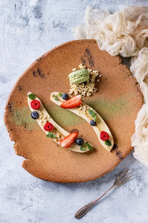 Food plating dessert organic banana with fresh berries, mint, puffed rice and macaroon biscuit served with green tea matcha powder on terracotta plate. Gray texture background, textile gauze. Flat lay Stock Photo