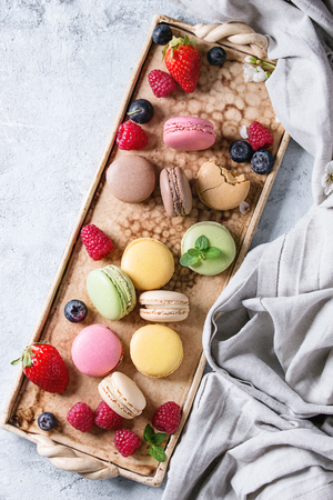 patisserie: Variety of colorful french sweet dessert macaron macaroons with different fillings served on terracotta tray with spring flowers, berries, textile over gray texture background. Top view with space