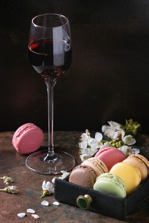 Glass of port wine with variety of colorful french sweet dessert macaron macaroons with different fillings served with spring flowers over dark texture background. Stock Photo - 77410602