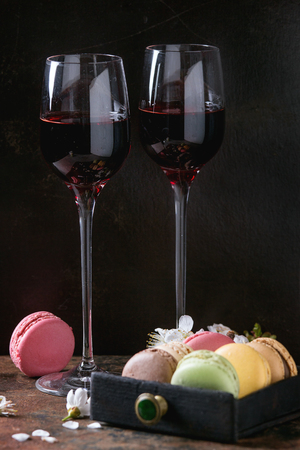 Two glasses of port wine with variety of colorful french sweet dessert macaron macaroons with different fillings served with spring flowers over dark texture background.