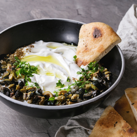 labneh middle eastern lebanese cream cheese dip with olive oil, salt, herbs, olives tapenade served in black bowl with traditional pita bread over gray texture metal background. Square image Stock fotó